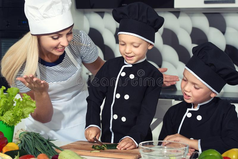 Una famiglia dei cuochi Cibo sano La madre ed i bambini felici della famiglia prepara l'insalata di verdure in cucina fotografie stock