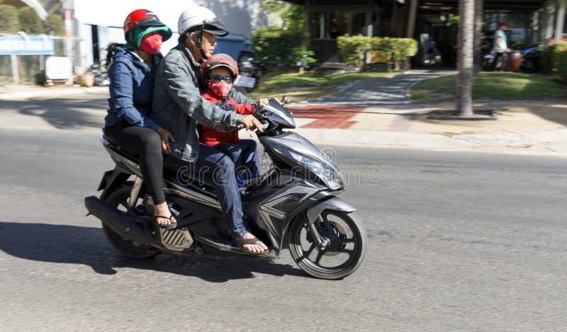 Una famiglia del viaggio tre su un singolo motorino di motore in Nam Tien, Vi fotografie stock libere da diritti