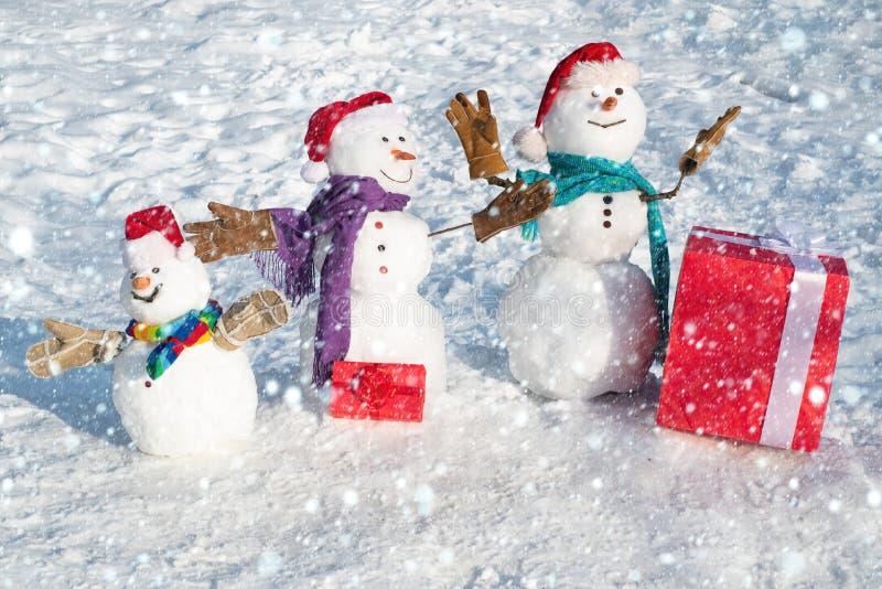 Una famiglia di nani eccitata con un sacco di regali Un pupazzo di neve in fondo ai fiocchi di neve Sfondo invernale immagine stock