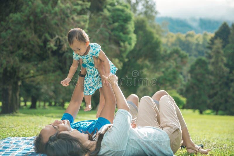 Una famiglia di tre con i happines della neonata che mette su un'erba fotografia stock libera da diritti