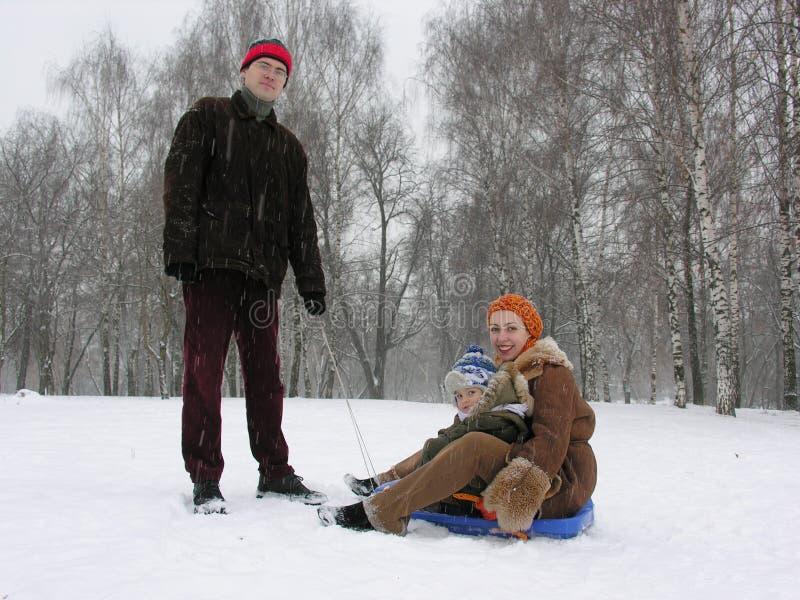 Una famiglia di tre con la slitta. inverno fotografia stock
