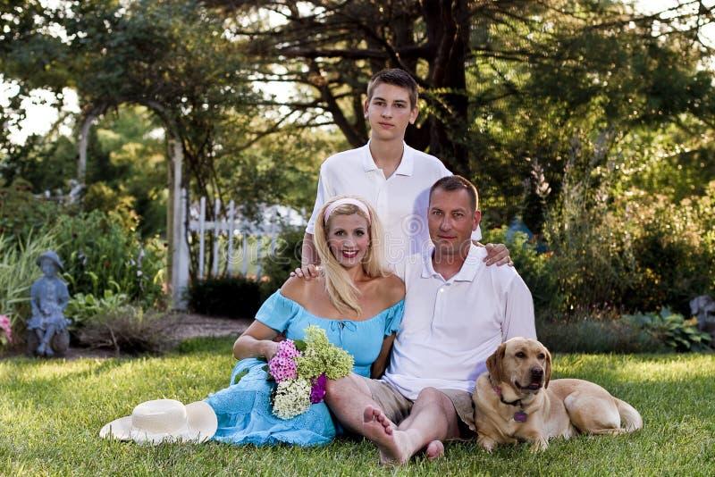 Una famiglia di tre davanti al giardino floreale fotografia stock