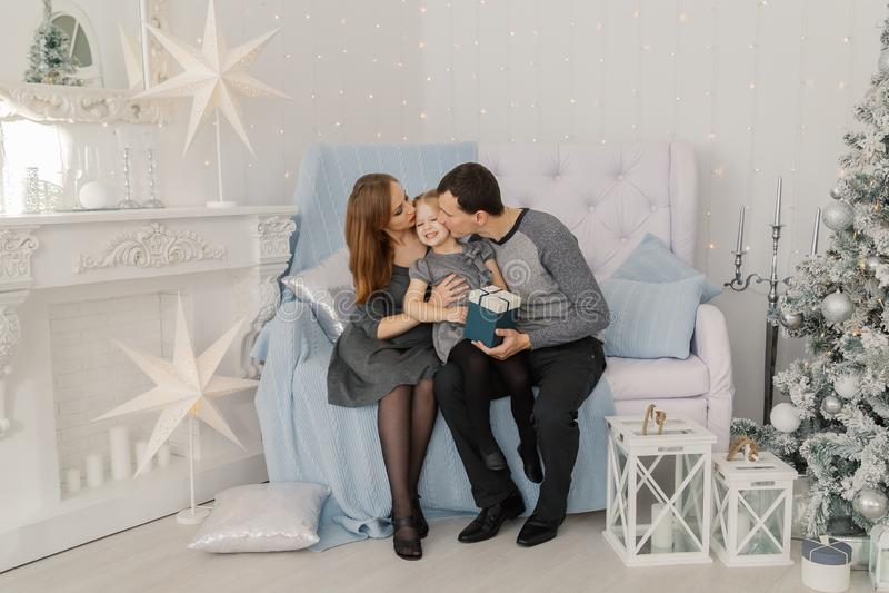 Una famiglia di tre felice e bella alla stanza di un nuovo anno intelligente festivo immagini stock