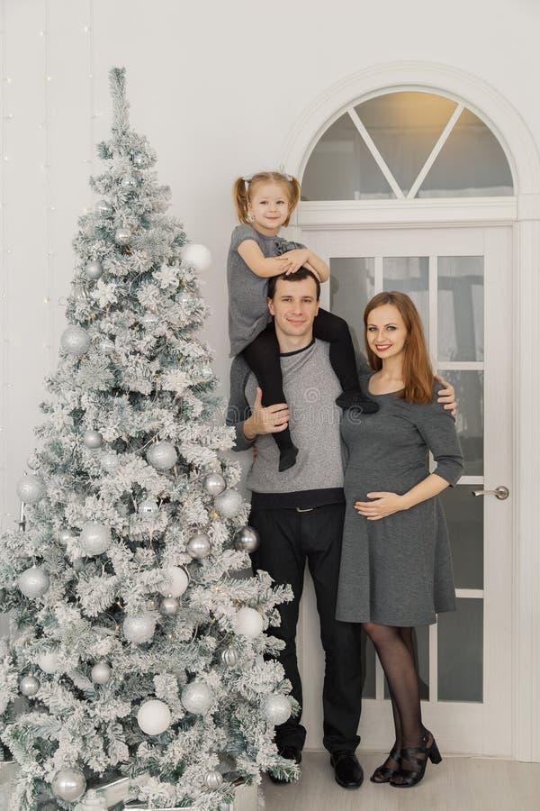 Una famiglia di tre felice e bella alla stanza di un nuovo anno intelligente festivo immagine stock libera da diritti