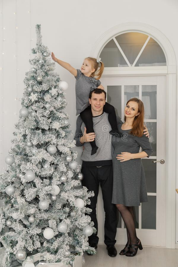 Una famiglia di tre felice e bella alla stanza di un nuovo anno intelligente festivo immagine stock