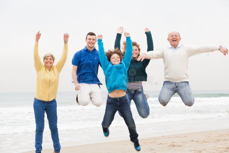 Una famiglia di tre generazioni che salta in aria fotografia stock