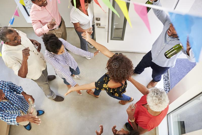 Una famiglia di tre generazioni ospiti di accoglienza di lancio della festa a sorpresa all'entrata principale, vista sopraelevata fotografia stock
