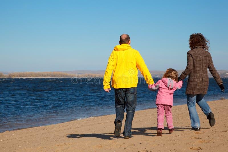 Una famiglia di tre genti che camminano lungo la spiaggia. fotografie stock libere da diritti