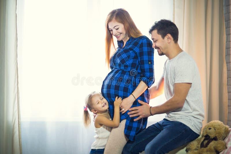 Una famiglia di tre Mamma incinta, papà e piccola figlia fotografie stock libere da diritti