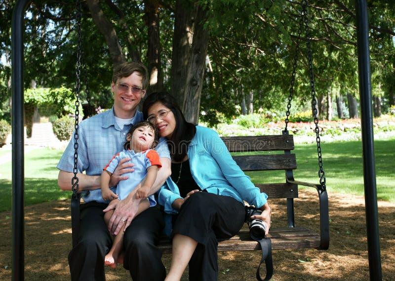 Una famiglia di tre su oscillazione fotografia stock