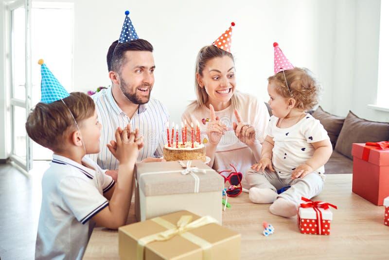 Una famiglia felice con il dolce celebra una festa di compleanno immagini stock libere da diritti