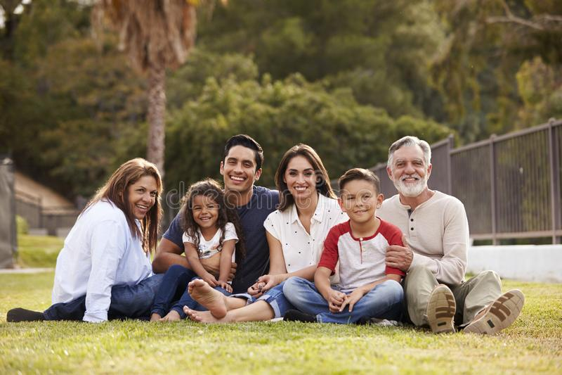 Una famiglia ispana di tre generazioni che si siede sull'erba nel parco che sorride alla macchina fotografica, fuoco selettivo fotografie stock