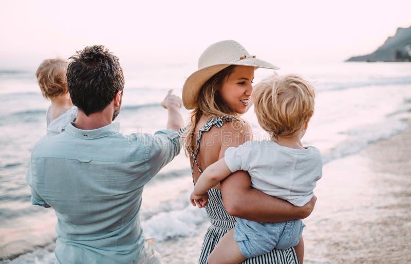Una familia con dos ni?os del ni?o que caminan en la playa el vacaciones de verano en la puesta del sol fotografía de archivo libre de regalías