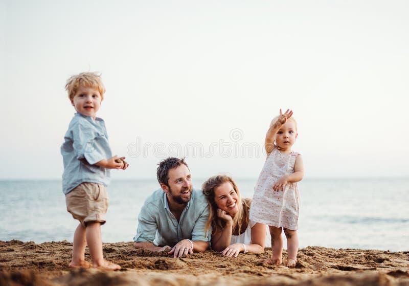 Una familia con dos ni?os del ni?o que mienten en la playa de la arena el vacaciones de verano imagen de archivo libre de regalías