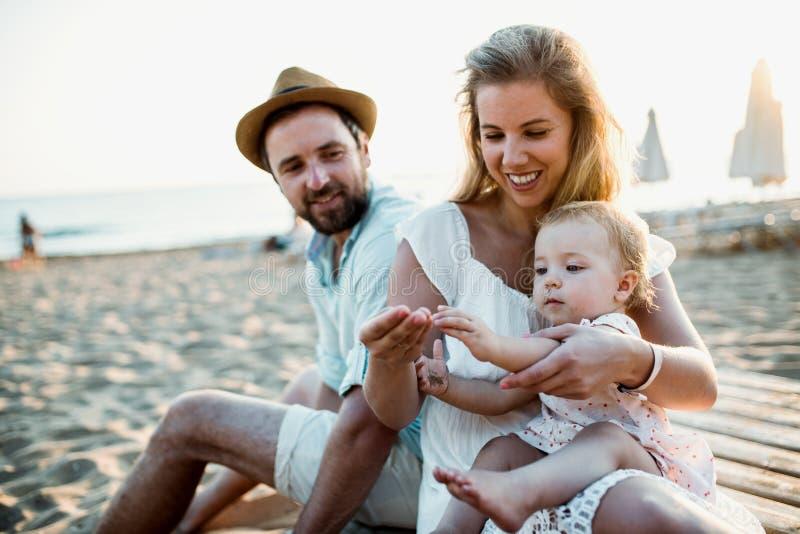 Una familia con una niña pequeña que se sienta en la playa de la arena el vacaciones de verano fotografía de archivo libre de regalías
