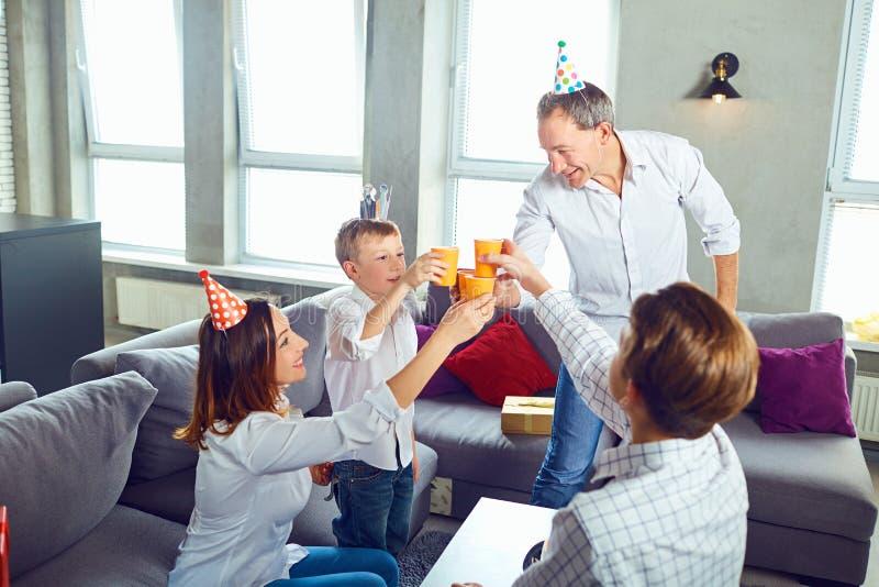 Una familia con una torta de la vela celebra una fiesta de cumpleaños fotos de archivo libres de regalías