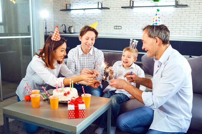 Una familia con una torta de la vela celebra una fiesta de cumpleaños foto de archivo