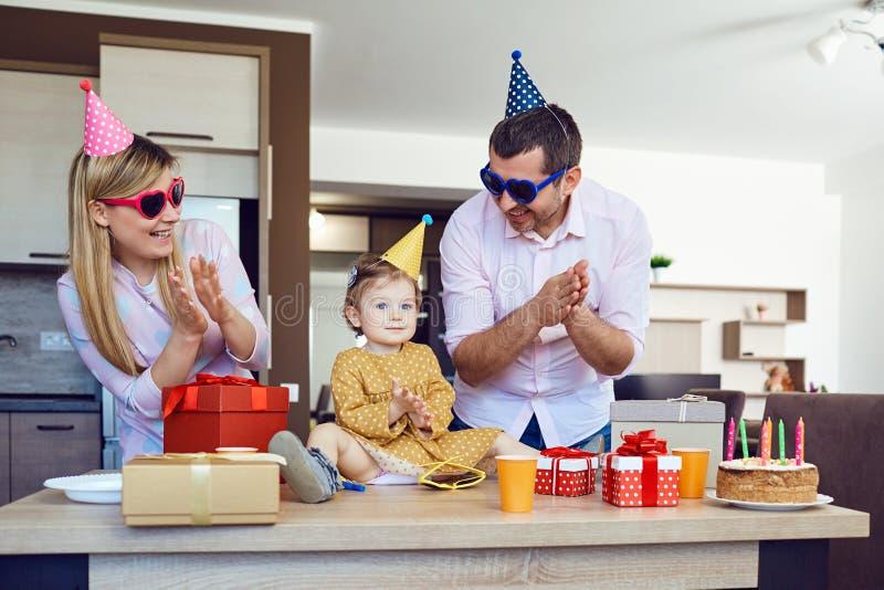 Una familia con una torta felicita a un niño feliz en su cumpleaños imagenes de archivo