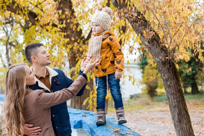 Una familia con un muchacho joven en el paseo del bosque del otoño imagen de archivo libre de regalías