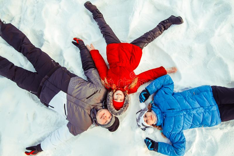 Una familia con un niño que miente en la nieve imagenes de archivo