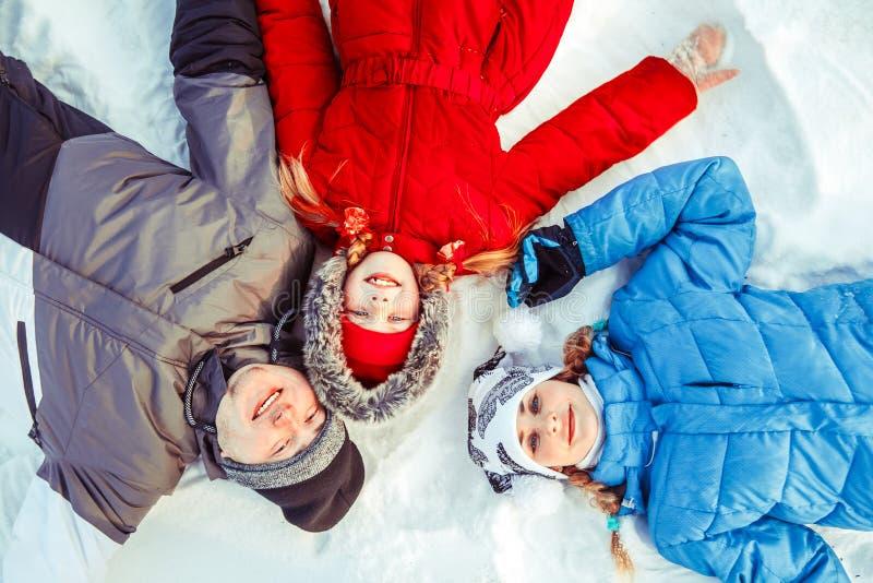 Una familia con un niño que miente en la nieve imagen de archivo libre de regalías