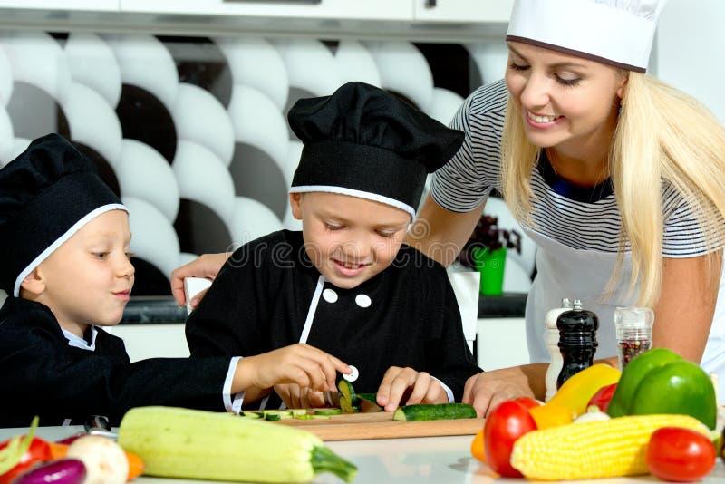 Una familia de cocineros Consumición sana La madre y los niños felices de la familia prepara la ensalada vegetal en cocina imágenes de archivo libres de regalías