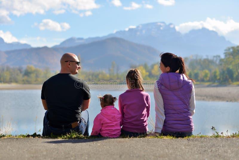 Una familia de cuatro miembros se sienta cerca del lago en el fondo de montañas fotografía de archivo libre de regalías