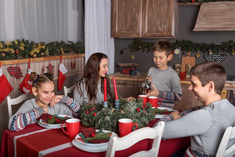 Una familia de fours en una tabla festiva del Año Nuevo que habla para divertirse, el hijo vierte té de la caldera imagen de archivo