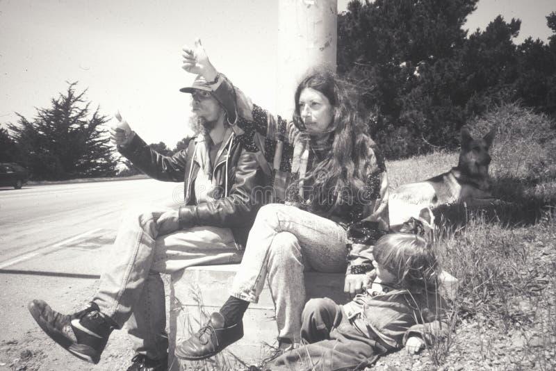 Una familia del hippie que hace autostop en la carretera 1 foto de archivo libre de regalías