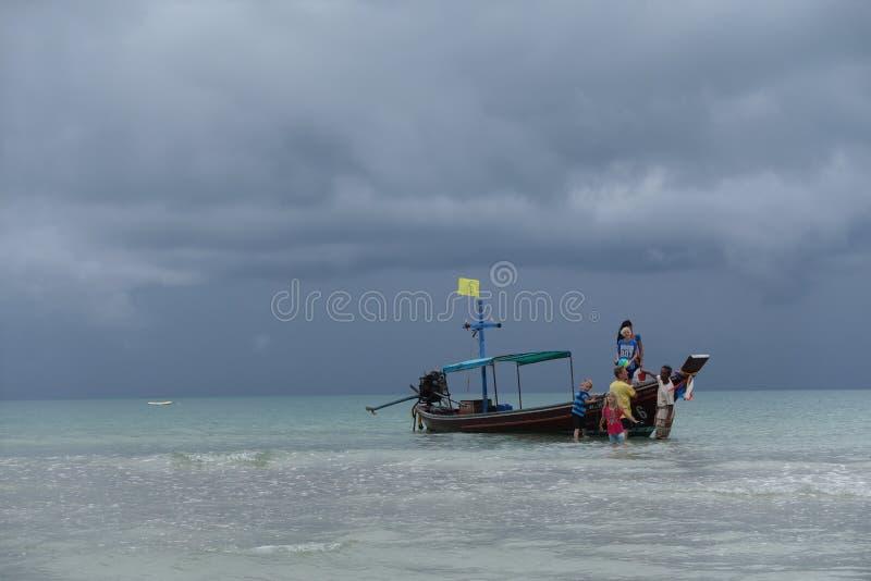 Una familia descarga del barco de la cola larga mientras que la lluvia se acerca en la KOH Phangan (Koh Pha Ngan) Tailandia foto de archivo libre de regalías