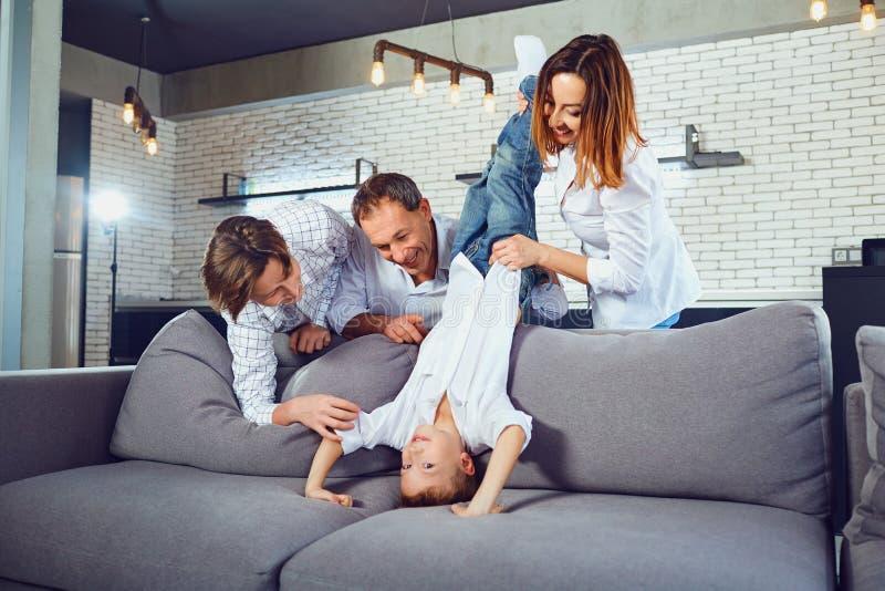 Una familia está jugando en el sofá en el cuarto foto de archivo libre de regalías