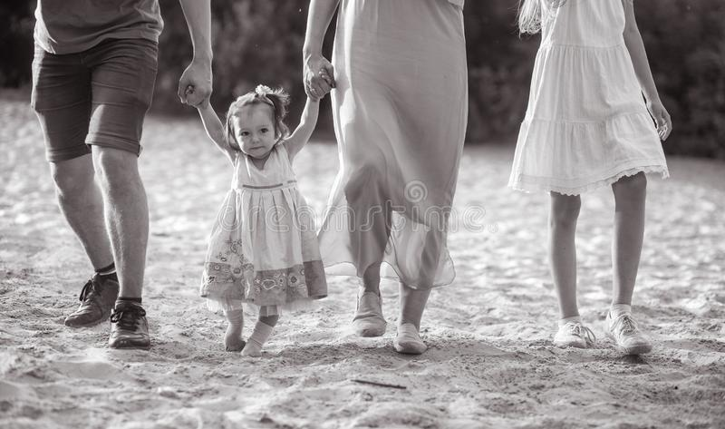 Una familia feliz con poco bebé va y lleva a cabo las manos mientras que camina foto de archivo