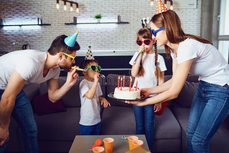 Una familia feliz con una torta de la vela celebra una fiesta de cumpleaños imagen de archivo libre de regalías
