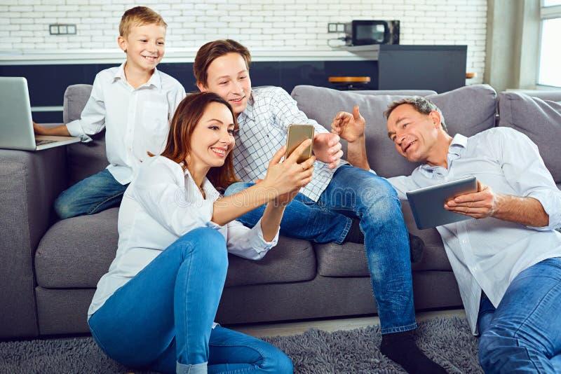Una familia feliz con un ordenador portátil se está divirtiendo en el cuarto fotos de archivo libres de regalías