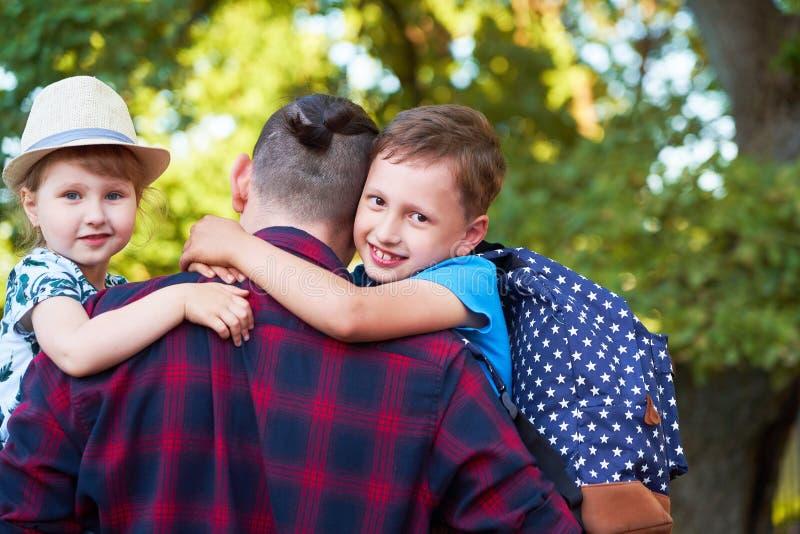 Una familia feliz de padre y de niños El papá está en las manos de niños en escuela primaria Padre, hijo e hija en el otoño foto de archivo libre de regalías