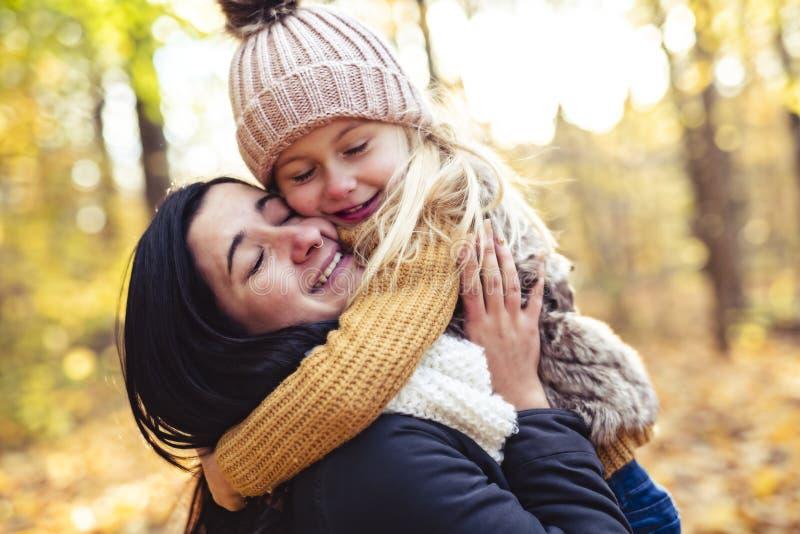 Una familia feliz el otoño, madre e hija en el parque fotos de archivo