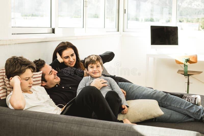 Una familia feliz que juega y que sonríe en el sofá en casa Concepto de amor entre los padres y los niños fotos de archivo libres de regalías