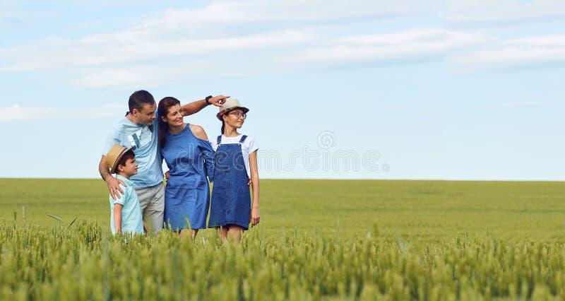 Una familia feliz que se coloca en un campo de trigo en verano imagenes de archivo