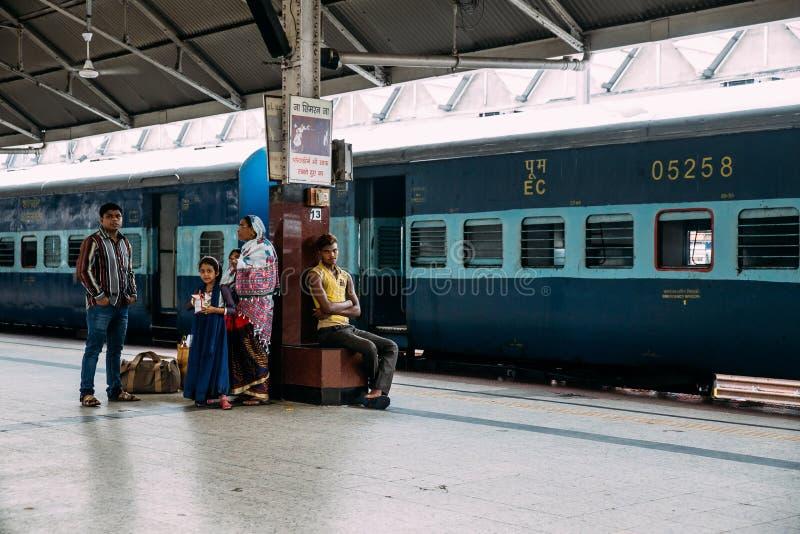 Una familia india que espera el tren en la plataforma para viajar dentro del ferrocarril del empalme de Howrah en Kolkata, la Ind fotos de archivo libres de regalías