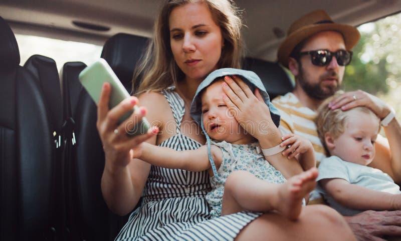 Una familia joven con dos ni?os del ni?o en taxi el vacaciones de verano imagenes de archivo