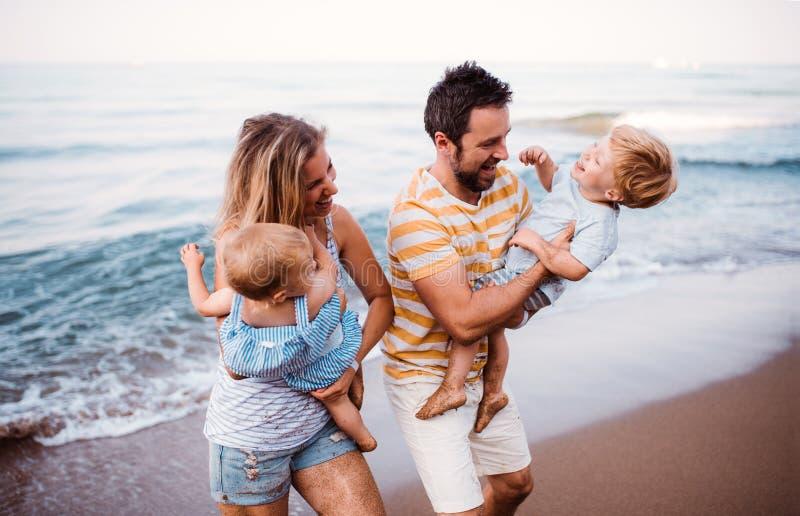 Una familia joven con dos ni?os del ni?o que caminan en la playa el vacaciones de verano imagen de archivo