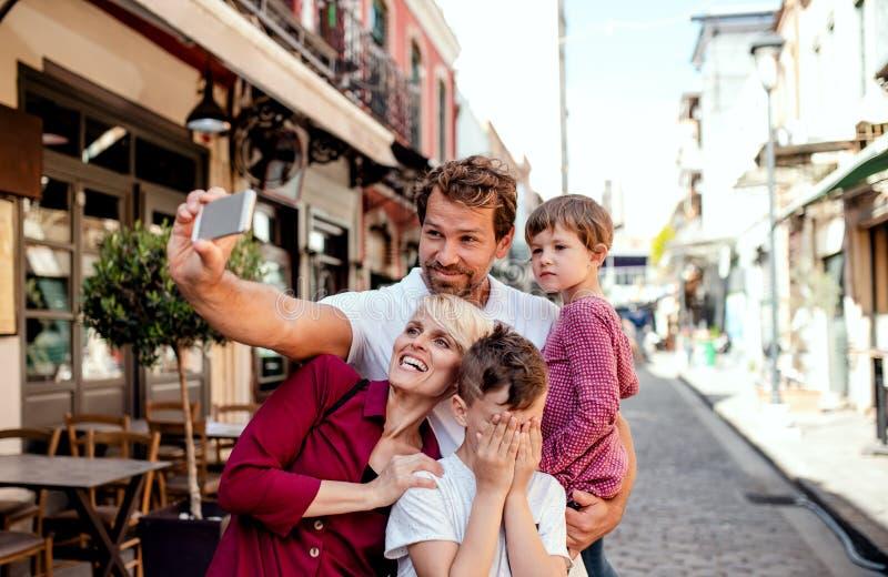 Una familia joven con dos pequeños niños que se colocan al aire libre en la ciudad, tomando el selfie imagen de archivo libre de regalías