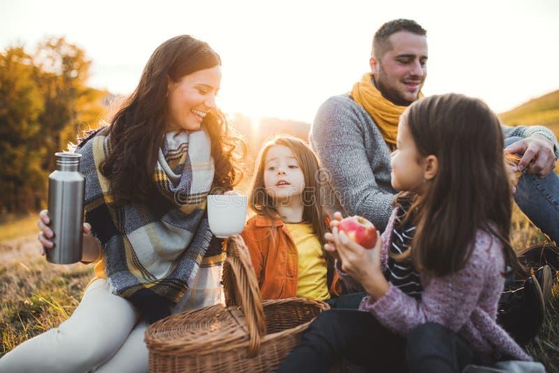 Una familia joven con dos pequeños niños que tienen comida campestre en naturaleza del otoño en la puesta del sol fotos de archivo libres de regalías