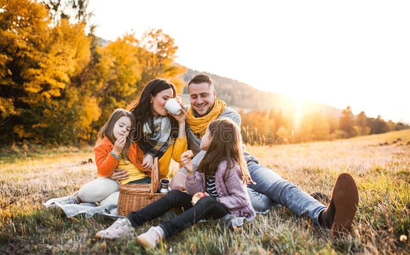 Una familia joven con dos pequeños niños que tienen comida campestre en naturaleza del otoño en la puesta del sol fotografía de archivo libre de regalías