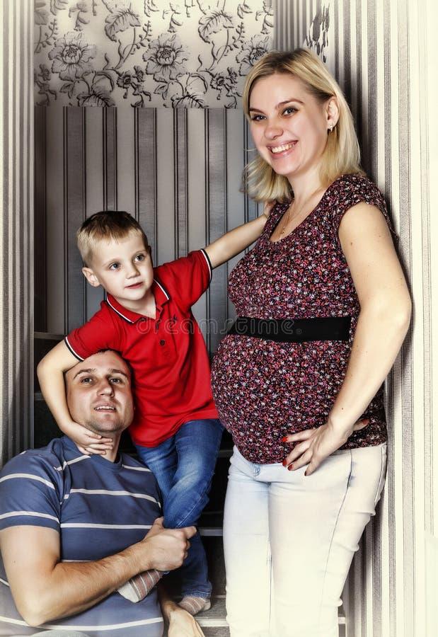 Una familia joven con una madre embarazada y un pequeño hijo fotografía de archivo