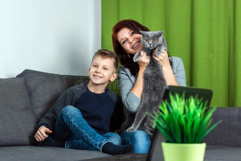 Una familia, una madre, un hijo y un gato felices se están sentando en la sensación del sofá feliz Familia inferior del concepto, fotos de archivo
