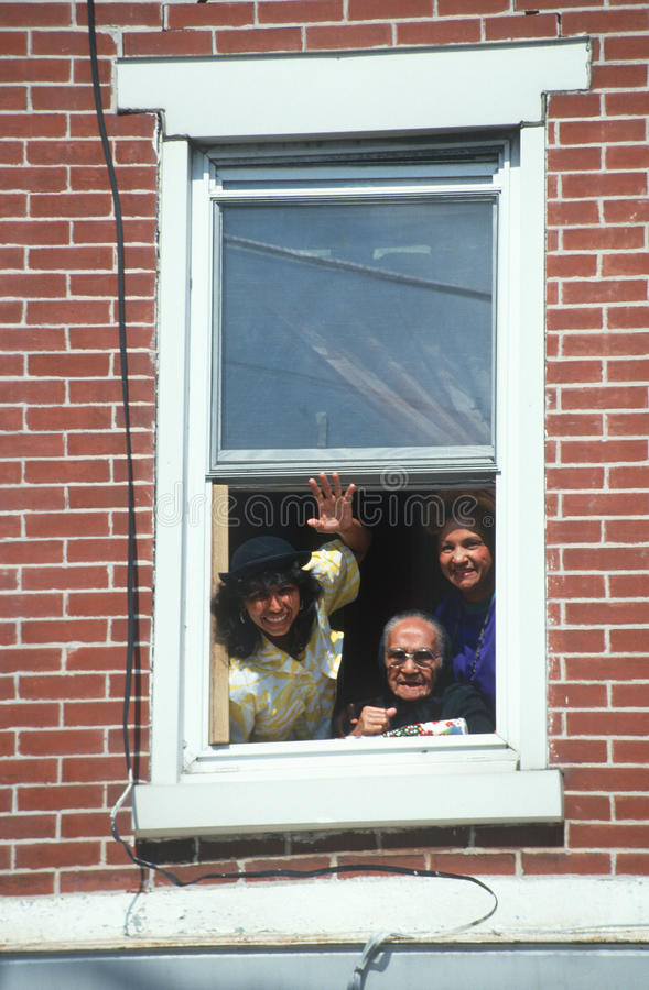 Una familia puertorriqueña que agita de su ventana del apartamento, Wilmington, DE foto de archivo