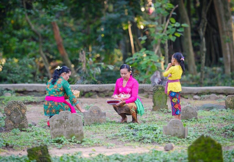 Una familia que hacía ofrendas a un difunto amó uno en el ubud, Bali fotografía de archivo