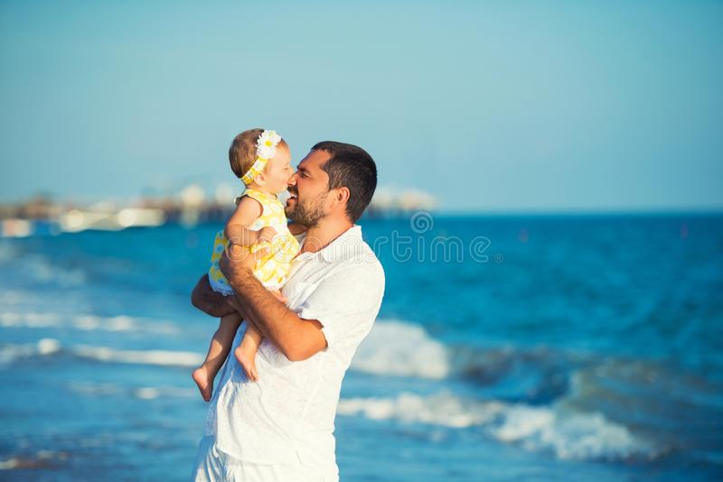 Una familia, un padre y una hija felices están jugando Una pequeña hija muerde a su papá por la nariz fotos de archivo libres de regalías