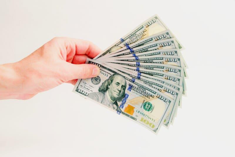 Una fan de las cuentas del ciento-dólar Mil dólares en la mano masculina izquierda en un fondo blanco Cómo ganar y cobrar el dine foto de archivo libre de regalías